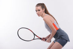 Tennis woman player with racket. Ready to win. Side view portrait of beautiful young woman in sports clothes holding tennis racket and looking at camera while Stock Photo