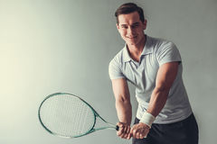 Tennis. Young sports man. Man tennis player on a gray background Royalty Free Stock Images