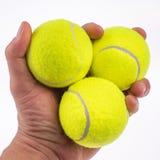 Tennisbälle in einer Hand mit einem weißen Hintergrund Lizenzfreies Stockbild