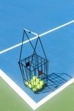 Tennisbaan met een van het balmand en tennis ballen daarin Stock Fotografie