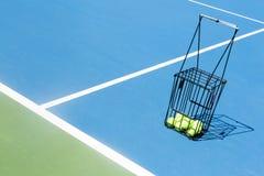 Tennisbaan met een van het balmand en tennis ballen daarin Royalty-vrije Stock Foto's