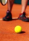 Tennisbaan met van de tennisbal en mens benen op achtergrond Stock Afbeelding