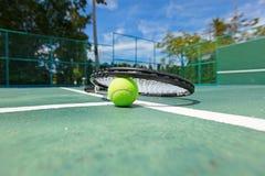 Tennisbal en racket op hof Stock Afbeeldingen