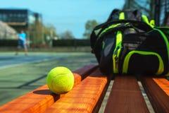 Tennisbal en sportzak op de bank op hof royalty-vrije stock afbeelding