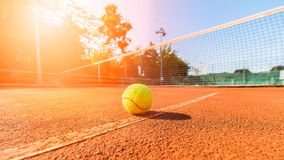 Tennisbal naast netto op kleihof Royalty-vrije Stock Fotografie