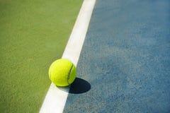 Tennisbal op een tennisbaan op een blauwgroen gebied als achtergrond royalty-vrije stock afbeeldingen