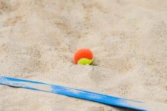 Tennisbal op het zand bij strand dichte omhooggaand royalty-vrije stock fotografie