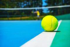 Tennisbal op witte hoflijn op hard modern blauwgroen hof met speler, netto, ballen, bomen op de achtergrond stock afbeelding