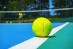Tennisbal op witte hoflijn op hard modern blauwgroen hof met speler, netto, ballen, bomen op de achtergrond stock foto's