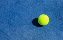 Tennisball auf blauem Hartplatz stockfoto