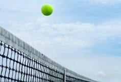 Tennisball, der über mittleres Nettogericht auf blauem Himmel des Hintergrundes fliegt stockbild