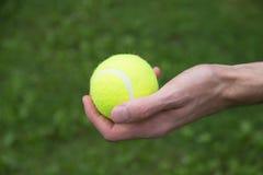 Tennisball in der Mannhand lizenzfreie stockbilder