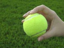 Tennisball in der menschlichen Hand Stockfotografie