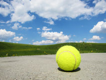 Tennisball and landscape. A yellow tennisball with landscape, green meadow and blue sky with clouds Royalty Free Stock Images