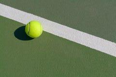Tennisball nahe bei Linie auf Hartplatz Lizenzfreie Stockfotos