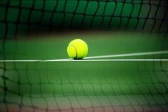 Tennisball setzte an einen Tennisplatz- und Netzhintergrund Lizenzfreie Stockfotos