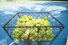 Tennisballen in de mand op tennisbaan Stock Afbeeldingen