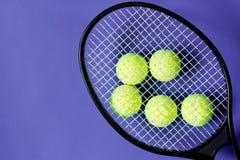 Tennisballen onder zwart racket Violette achtergrond Conceptensport Stock Fotografie
