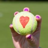 Tennisballliebesherz, das vom Tennisspieler gehalten wird Lizenzfreie Stockfotografie