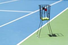 Tennisbana med en bollkorg och tennisbollar i den Arkivbild