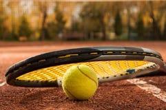 Tennisbegrepp med racket och bollen på leradomstolen Arkivbild