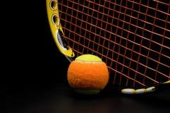 Tennisboll för ungar med tennisracket Arkivfoto