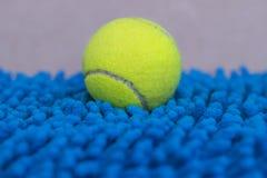 Tennisboll på de matta blåtten Royaltyfri Bild