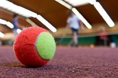 Tennisboll på den inomhus domstolen Royaltyfria Bilder