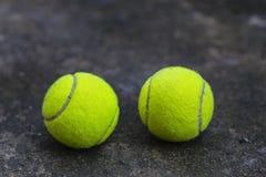 Tennisboll på den smutsiga jordningen Arkivbild