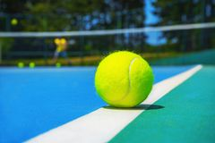 Tennisboll på den vita domstollinjen på den hårda moderna blåa gröna domstolen med spelaren som är netto, bollar, träd på bakgrun arkivfoton