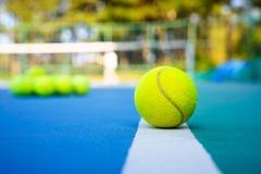 Tennisboll på den vita domstollinjen på den hårda moderna blåttdomstolen med spelareträd för netto bollar i bakgrunden royaltyfri fotografi