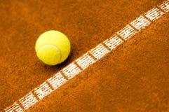 Tennisboll på en leradomstol Arkivbild