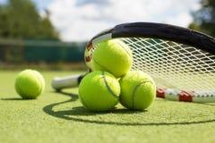 Tennisbollar och racket på gräsdomstolen Royaltyfri Foto