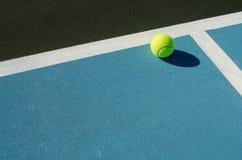 Tennisbollen vilar på den blåa tennisbanan royaltyfria foton
