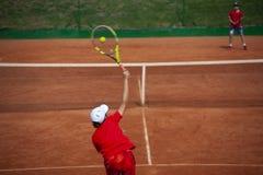 Tennisjongen het dienen binnen kiest tennistoernooien uit stock foto's