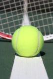 Tenniskugel mit Schlägerhintergrund Stockfotografie