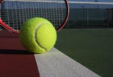 Tenniskugel und -schläger auf Gericht Stockfotos