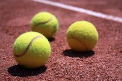 Tenniskugeln auf Schlackefeld Stockfotografie