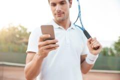 Tennismann mit Telefon lizenzfreie stockfotografie