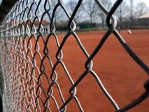 Tennisplatz im Kies angesehen durch den Schutzleitermaschendraht Stockfotografie