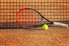 Tennisracket med en boll nära det netto på den jord- domstolen solig dag N?rbild royaltyfria bilder