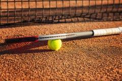 Tennisracket med en boll nära det netto på den jord- domstolen solig dag N?rbild royaltyfri foto