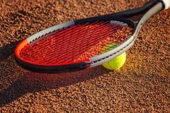 Tennisracket med en boll nära det netto på den jord- domstolen solig dag N?rbild royaltyfri bild
