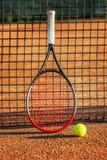 Tennisracket med en boll nära det netto på den jord- domstolen solig dag N?rbild arkivfoton