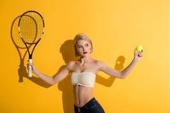 tennisracket och boll för härlig ung blond kvinna hållande royaltyfri fotografi