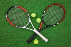Tennisschläger mit Bällen auf grünem Gras Lizenzfreies Stockfoto