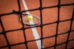 Tennisschläger und -ball auf Gericht durch Netz Stockbilder