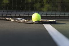 Tennisschläger und -ball durch Netz Lizenzfreie Stockfotografie