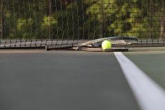 Tennisschläger und -ball durch Netz Stockfotografie