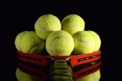 Tennisschläger und Stapel von Tennisbällen lizenzfreies stockbild